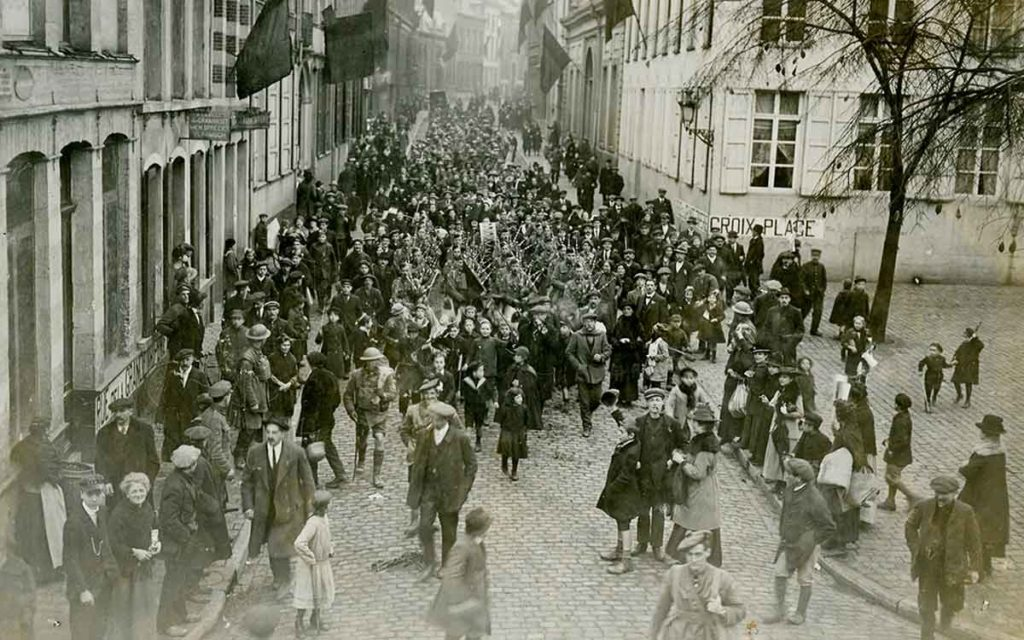 Canadian soldiers and local citizens march the streets of Mons. Credit: Canadian War Museum.
