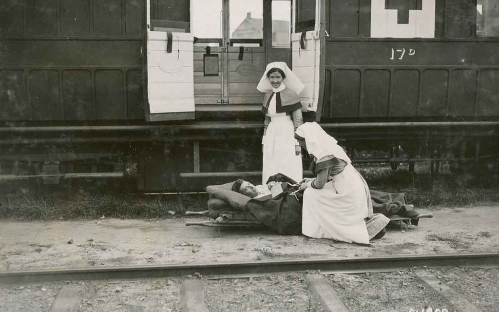 A pair of First Word War nurses help load a patient-soldier onto a train bound for England. Credit: Canadian War Museum.