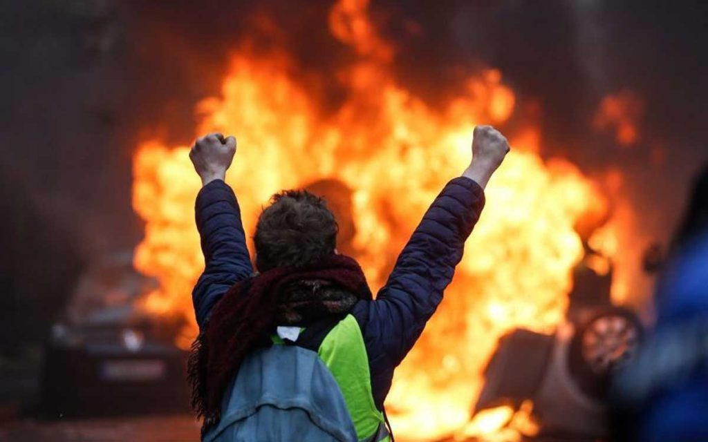 "A protester gestures in front of a burning vehicle as ""yellow vests"" (Gilets jaunes) protesters demonstrate against rising oil prices and living costs in Paris."