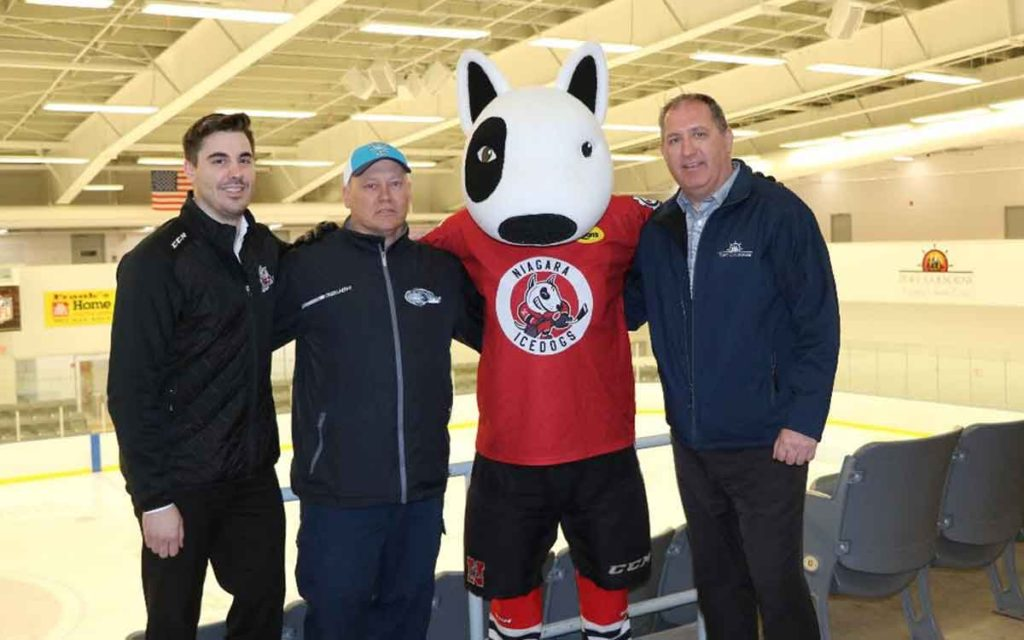 Port Colborne Mayor Bill Steele (far right) welcomes Niagara IceDogs mascot Bones to Port Colborne.