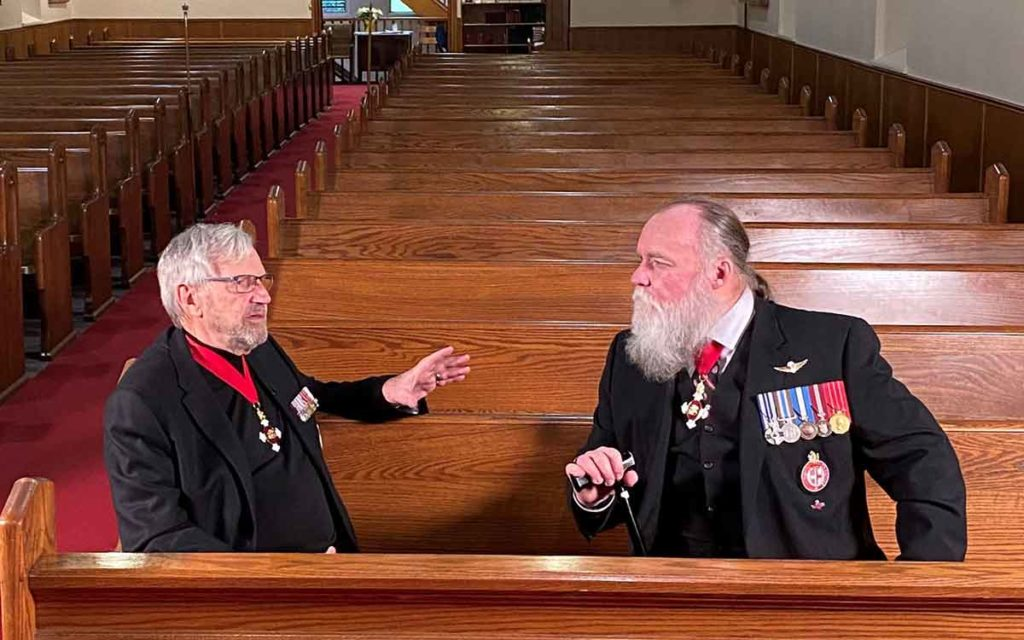Colonel Andrew Nellestynin and Paul Cane sitting in pews