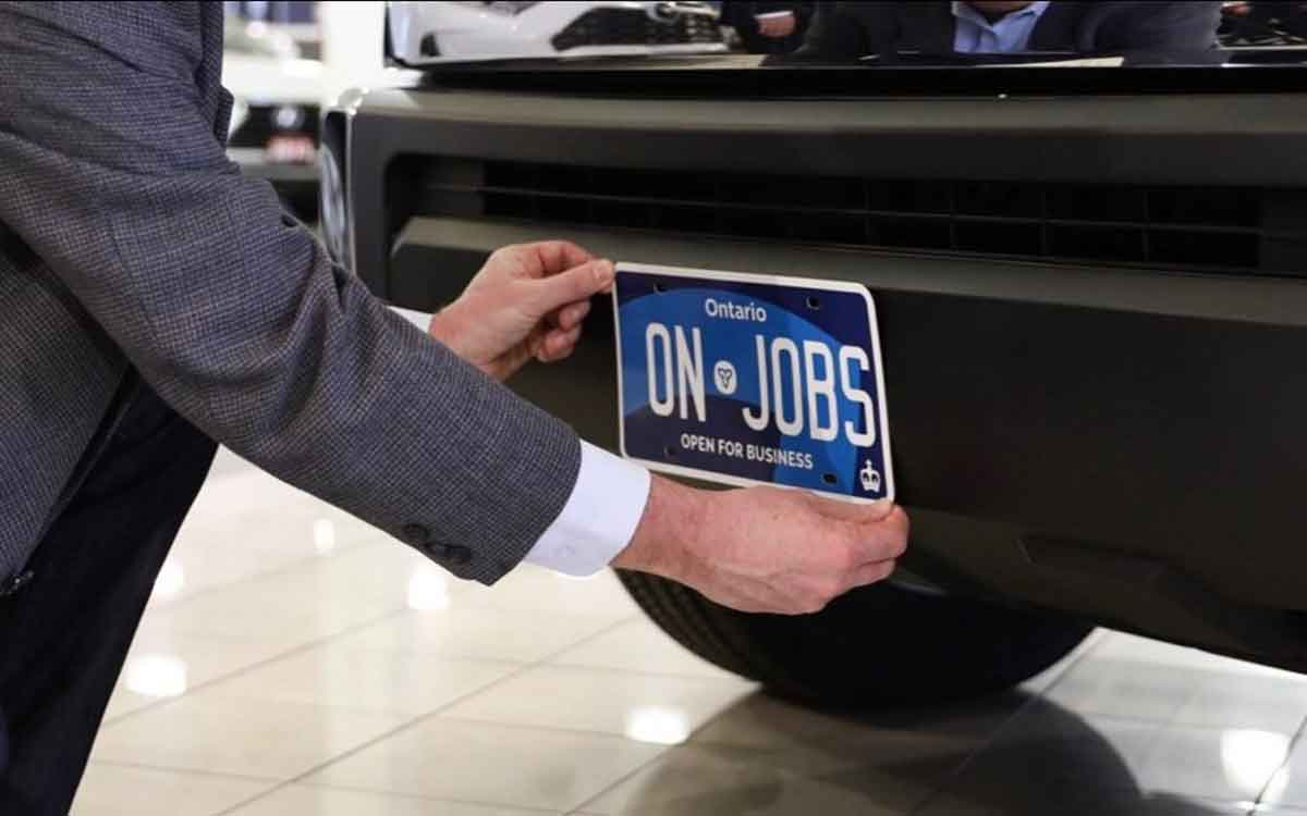 new Ontario license plate being placed on a car bumper