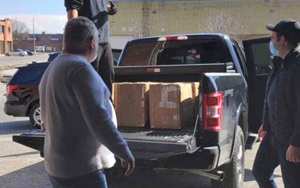 premier ford loading donated face masks into his truck