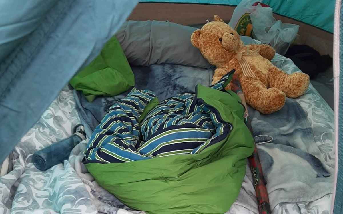 sleeping bag and teddy bear inside of a tent