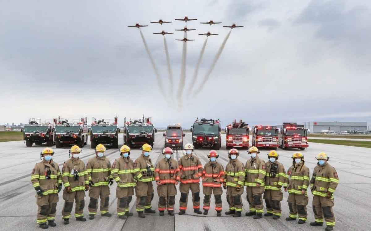 snowbirds flying over a group of firefighters