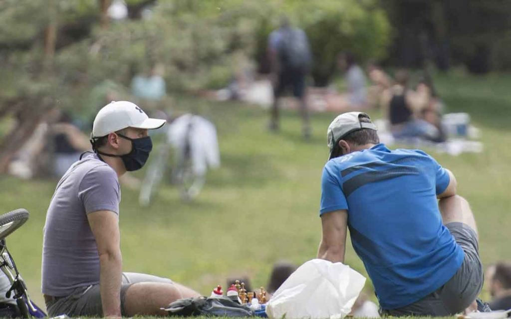 two people in a park wearing masking