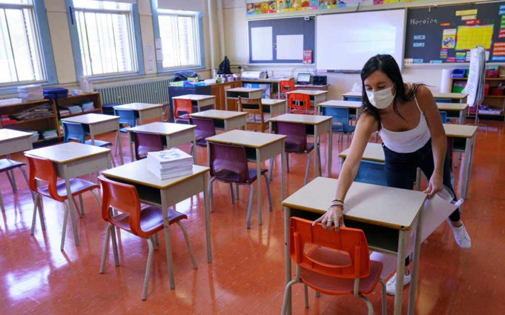 teacher wiping down desks in a classroom