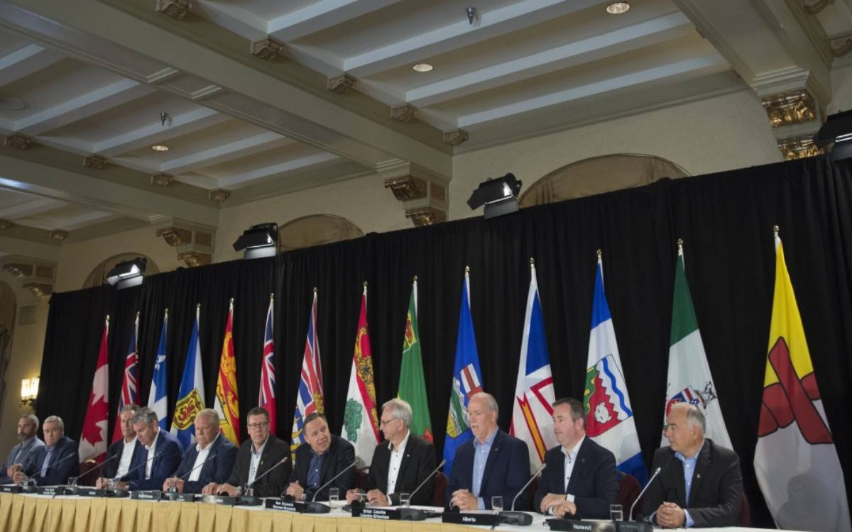 the premiers of canada sitting at a table during a meeting