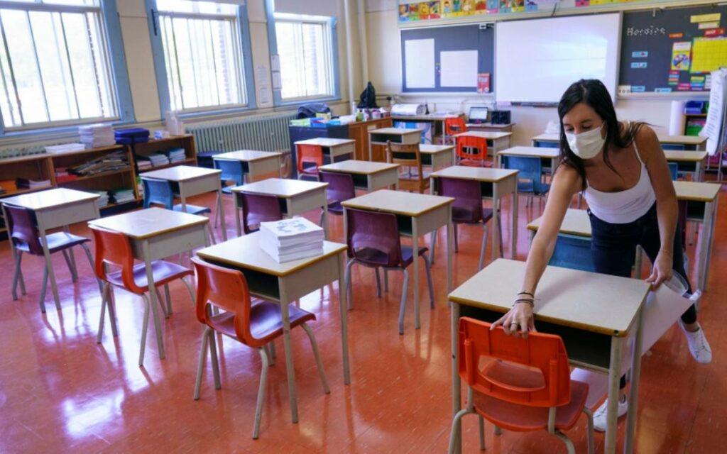 a teacher cleaning desks in a classroom