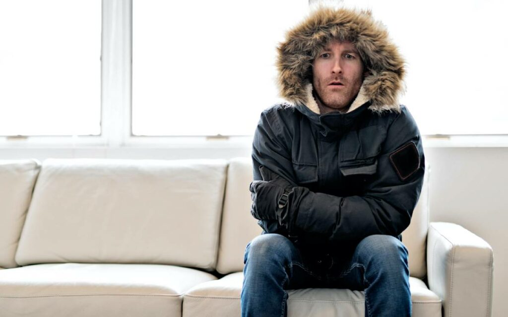 man wearing a parka on a couch